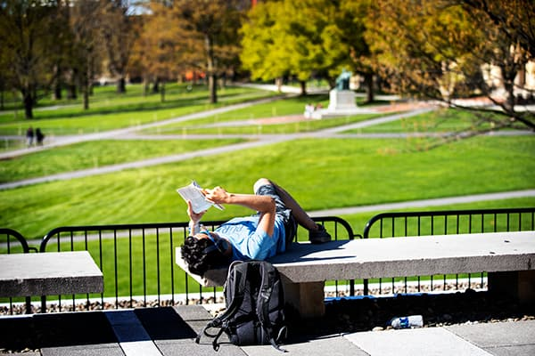 A student studies in the afternoon sun on the terrace above Olin Library.