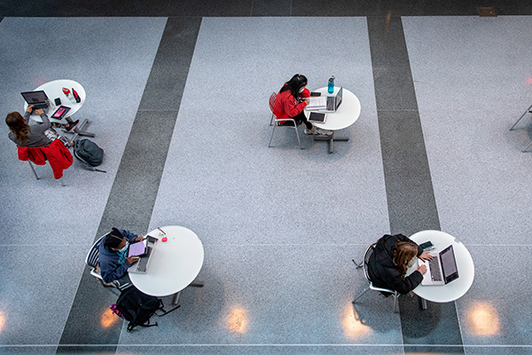 Students work at socially distant tables in the Physical Science Building