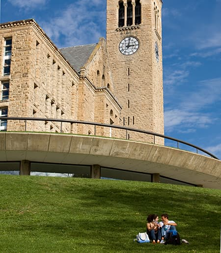 students sit on Lib Slope with Clock Tower in the background