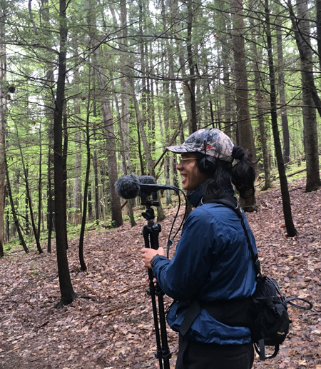 student in a forest with sound recording devices