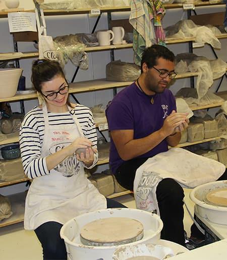 students at pottery wheels