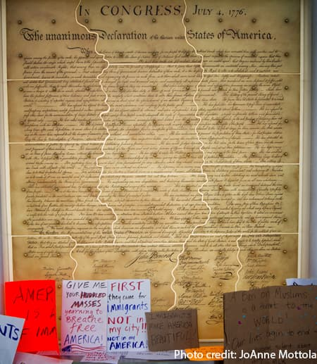 protest signs in front of large copy of the Declaration of Independence
